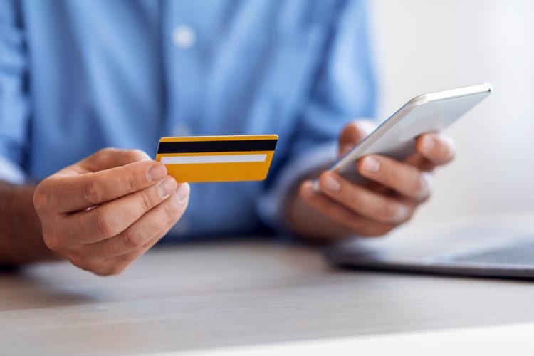 un hombre consulta su smartphone y su tarjeta de crédito