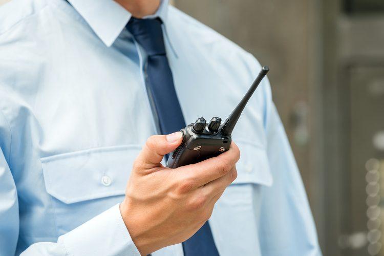 un vigilante de seguridad privada se comunica con un radio